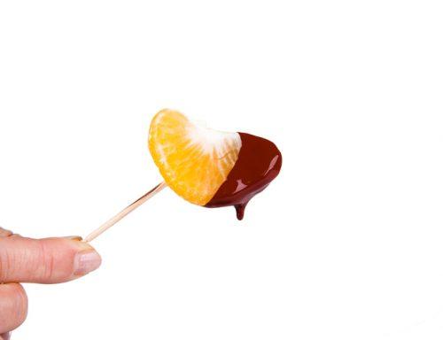 Mandarine dipped in melting dark chocolate