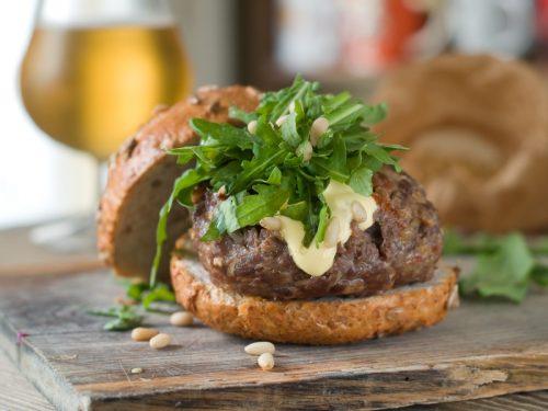 Hamburger with burger, arugula and pine nuts, selective focus