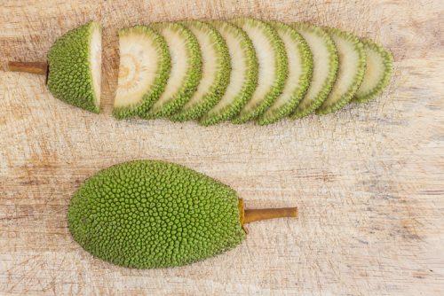 Sliced immature jackfruit on wooden chopper block