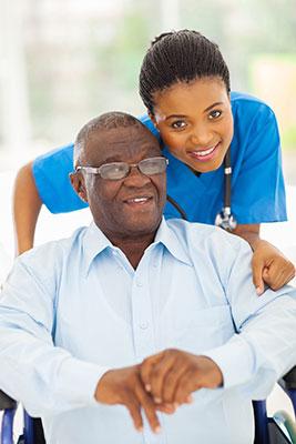 beautiful young black female caregiver in bright blue scrubs hugging elderly black man sitting in a wheelchair
