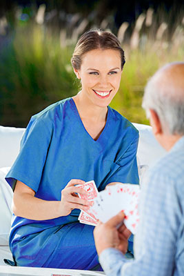 beautiful whil female caregiver in bright blue scrubs smiling and playing cards with an elderly man in a long-sleeved blue shirt