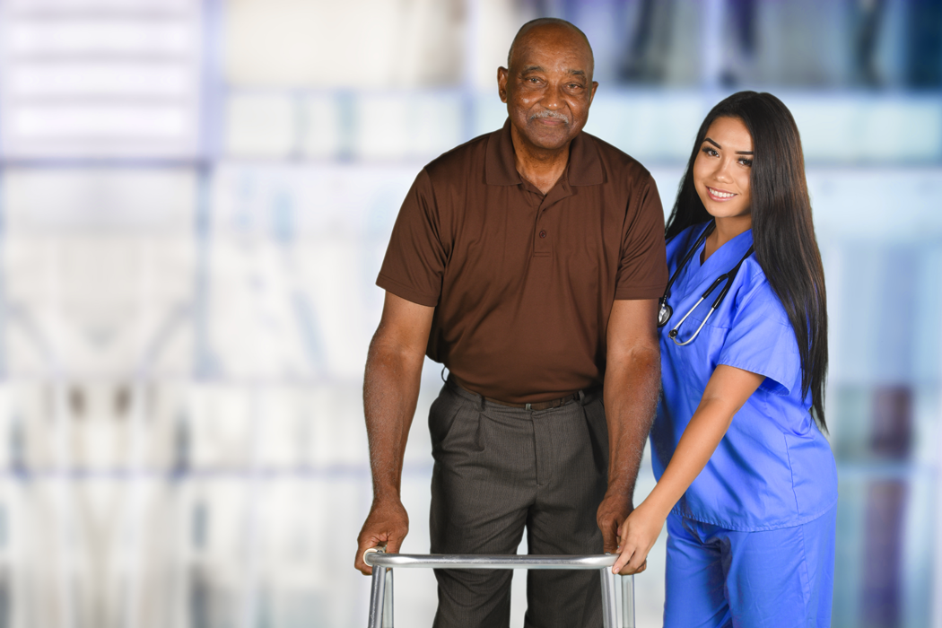 pretty hispanic girl in bright blue scrubs helping elderly black man in brown shirt and gray slacks to use his walker