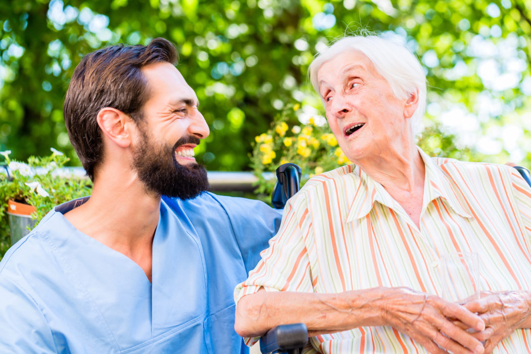 Nurse having chat with senior woman in nursing home