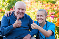 elderly white man sitting with a young pretty white female caregiver in blue scrubs with both giving a thumbs up