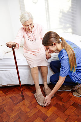 white female in bright blue scrubs wearing hair in a ponytail helps put an elderly woman's slippers on