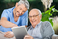 happy male caregiver in blue scrubs and smiling white senior man looking at ipad