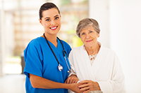 pretty white female caregiver in blue scrubs standing with an elderly white woman in a white robe