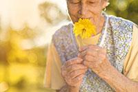 white senior woman smelling a bright yellow flower