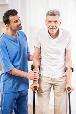 white man in bright blue scrubs helping an eldering man walk with canes