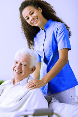 close up of pretty young black female caregiver standing with her hands on the shoulders of an elderly white man sitting in a wheelchair
