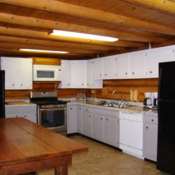 The Kitchen at Cedars Log Home includes amenities such as stove, microwave, 2 refrigerators, dishwasher, and coffeemakers