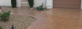 poured concrete driveway and sidewalk with gravel landscaping