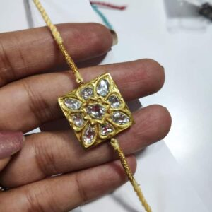 Gold Rakhi with Kundan Work and Decorative Back in hand