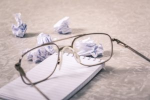 glasses on top of a note pad with balled up paper all around