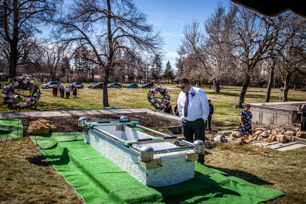 brother looking at hole in ground Wasatch lawn salt lake city cemetery photography for funerals Ryan hender films