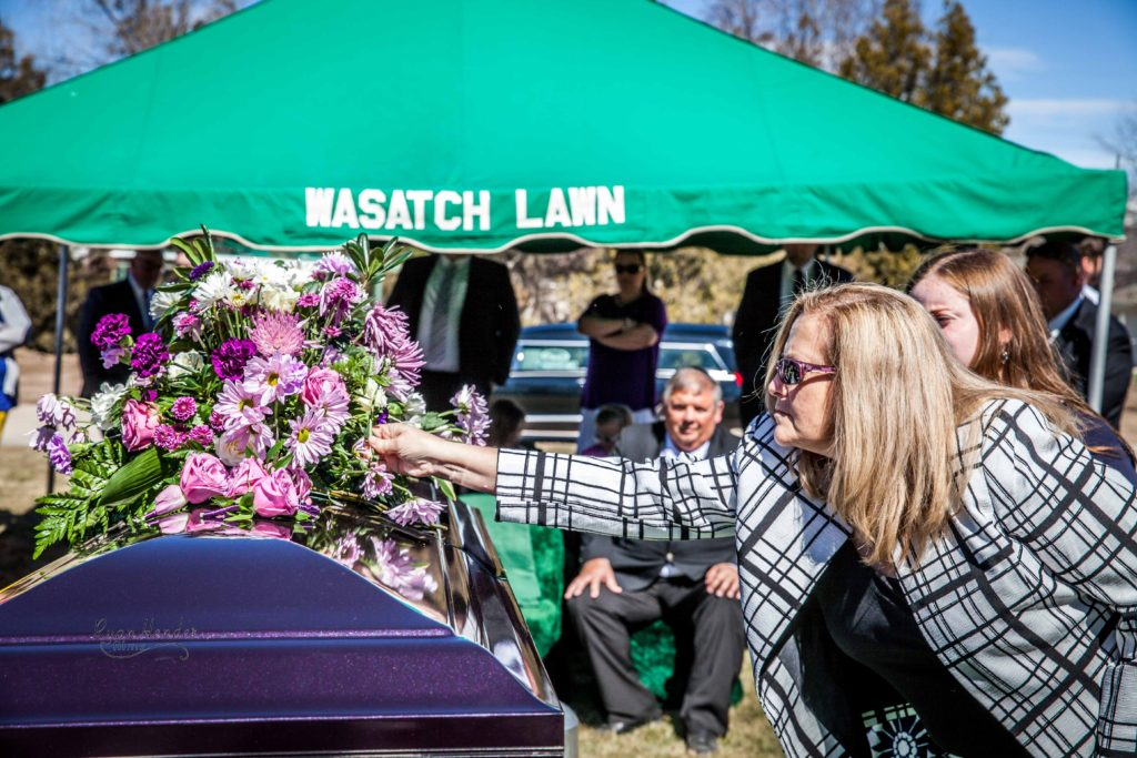 mother placing flower on casket Wasatch lawn salt lake city cemetery photography for funerals Ryan hender films