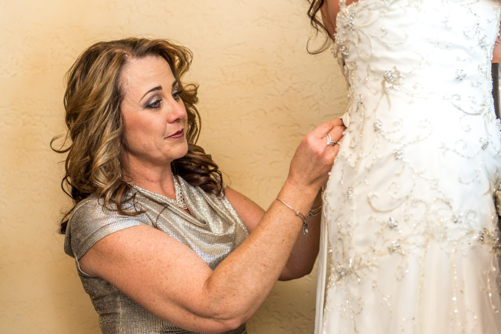 Mother of bride tying up back of Bride's dress