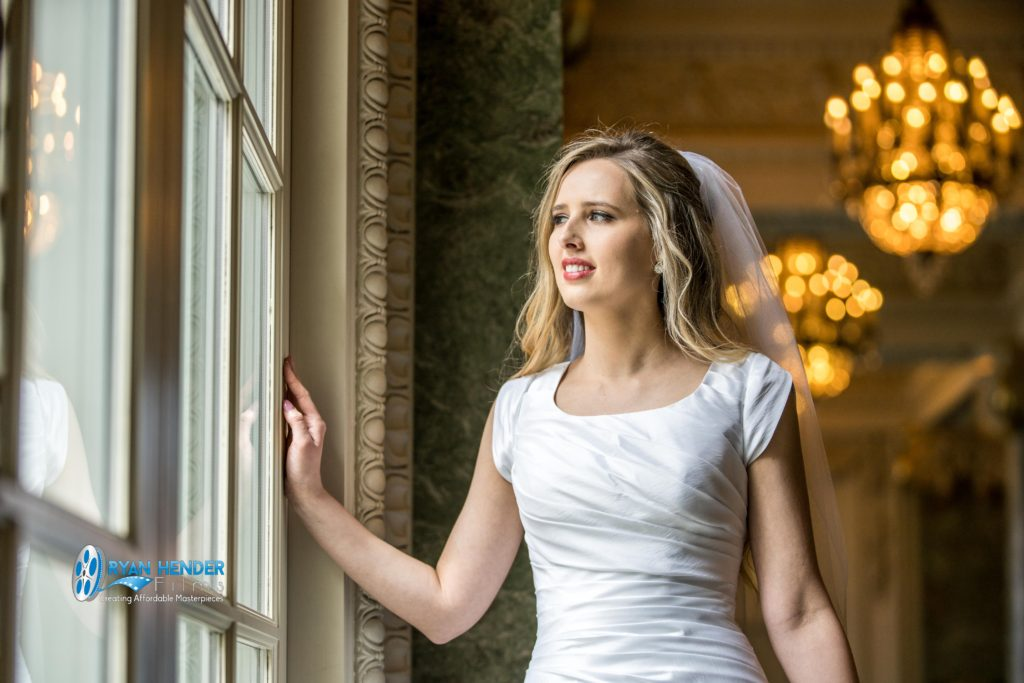 bride standing next to window wedding photography