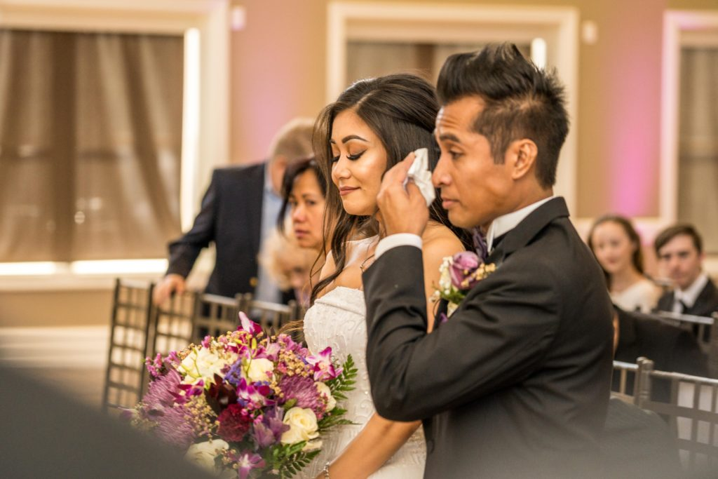 groom wiping tears from his cheek