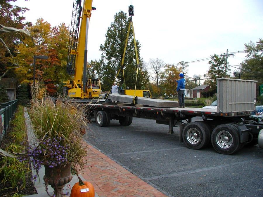 A crane lifting a water garden bridge rock