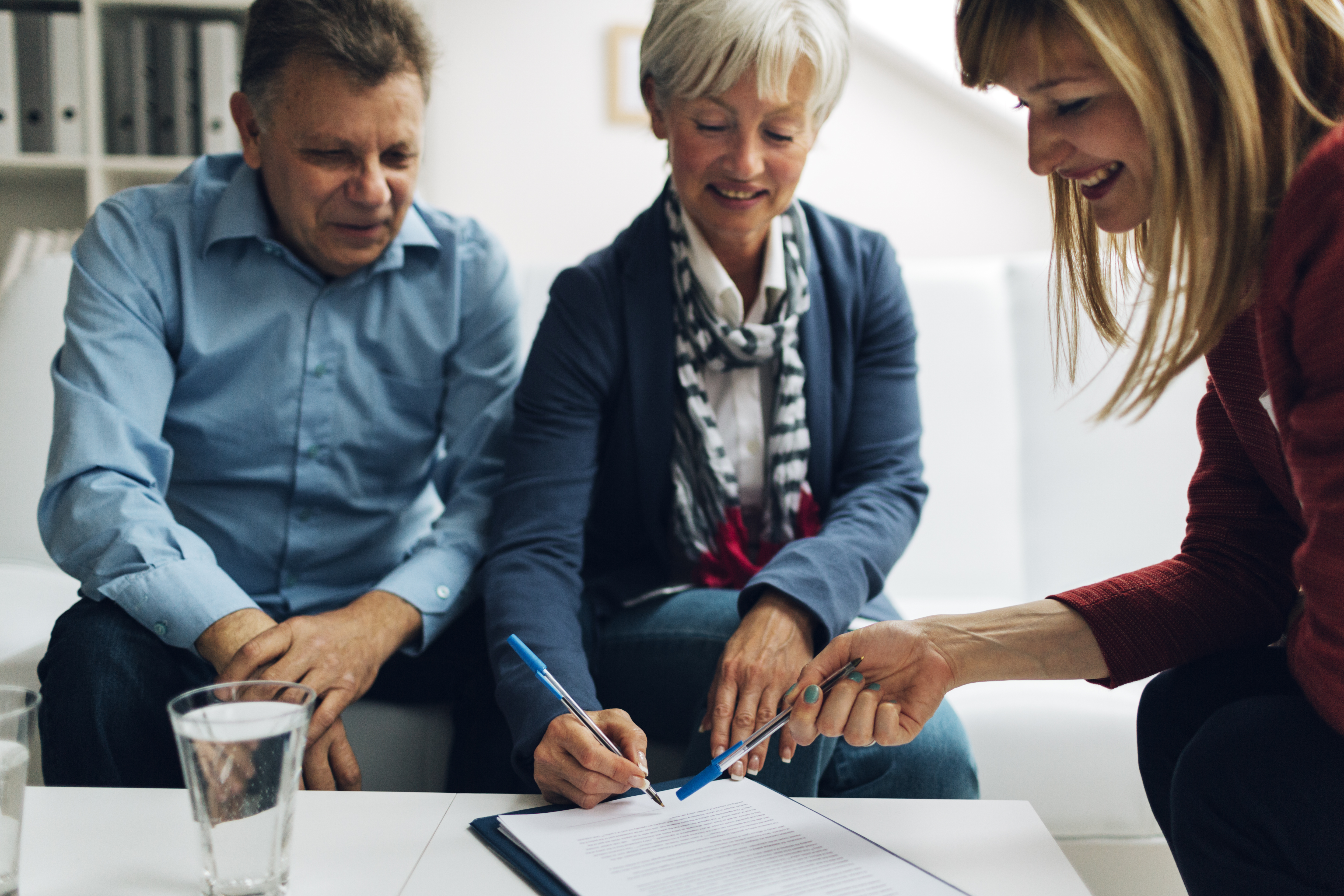 Mature Couple Meeting with Financial Advisor, selective focus to mature woman signing agreement.