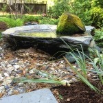 A dry pond with Goshen stone basin and a mossy rock from the property, rippling and soothing