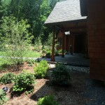 The Goshen stone porch accompanied by the plantings and lawn, a fine welcome