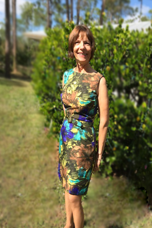 Susan Mann standing outside in front of a hedge in a multicolored dress
