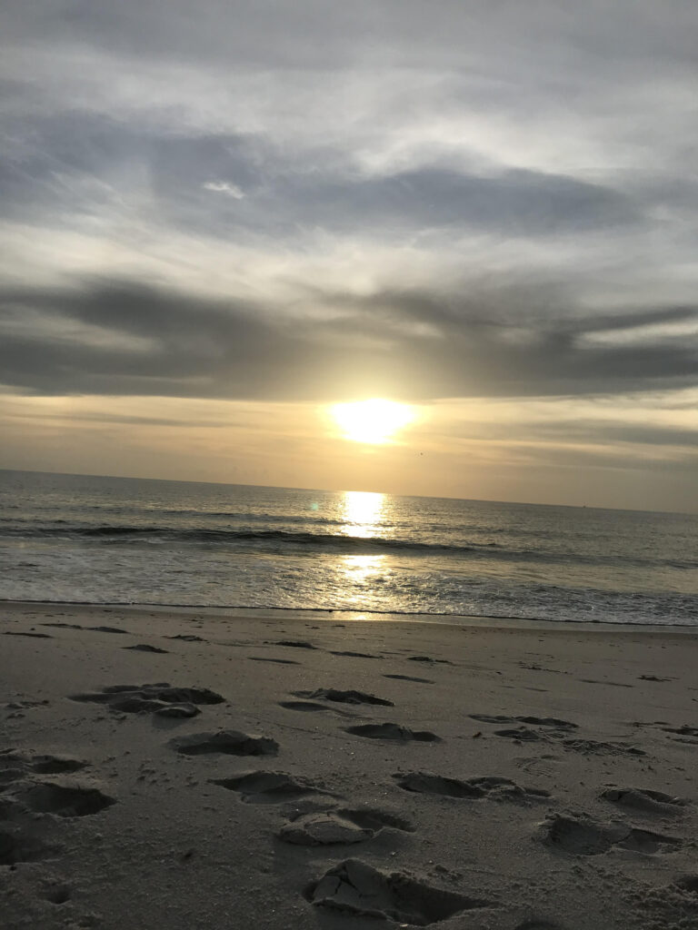 an overcast sky with an orange sun setting in the middle. water flows to the front of the picture and sand is in the foreground with small prints imprinted. A calm sense of hope and love is present.