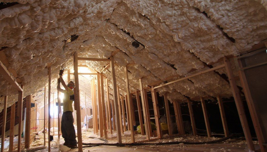 Foam Engineers trims back excess spray foam insulation from the roof rafters in this unvented attic assembly.