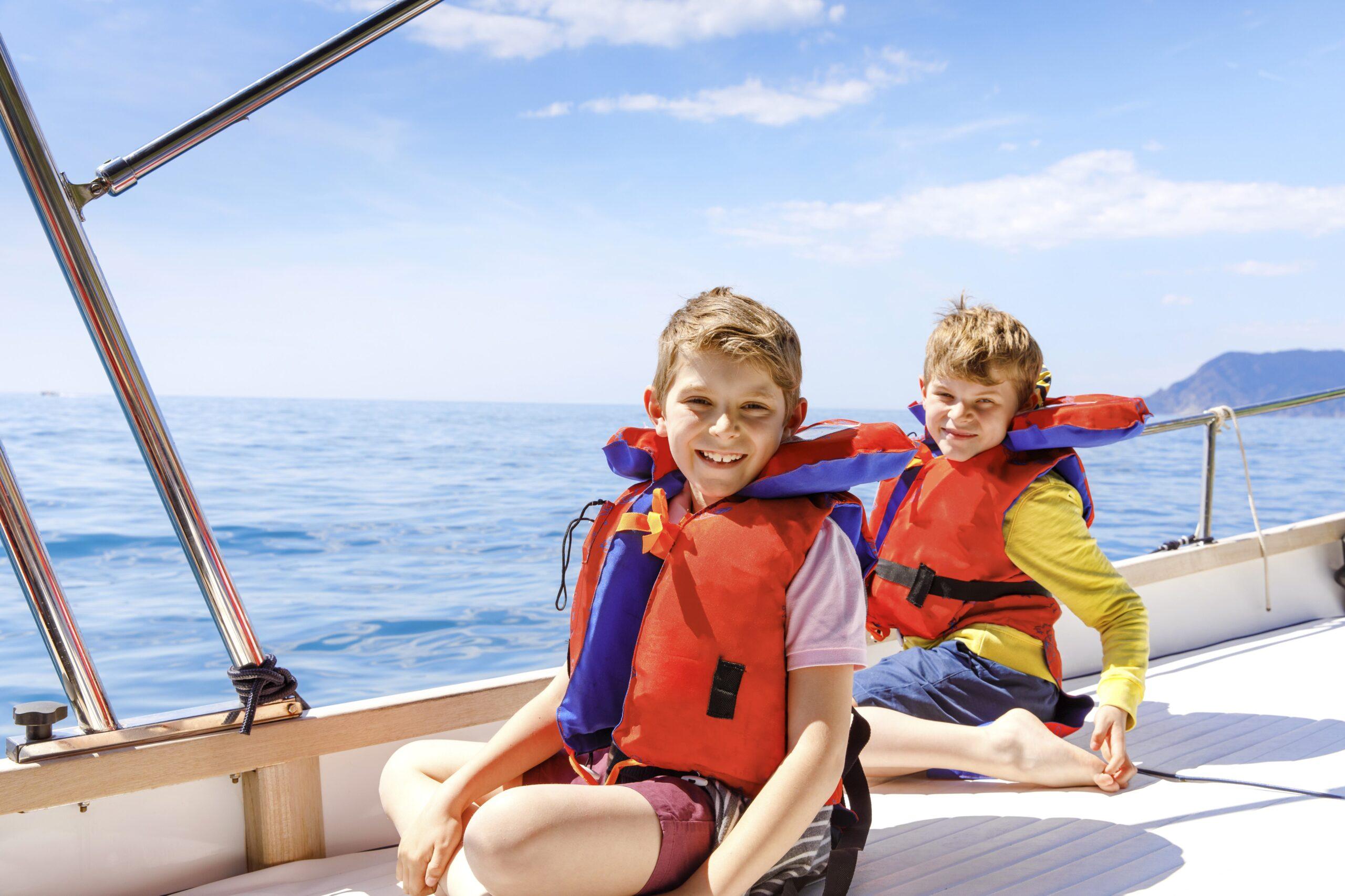 Two little kid boys, best friends enjoying sailing boat trip.