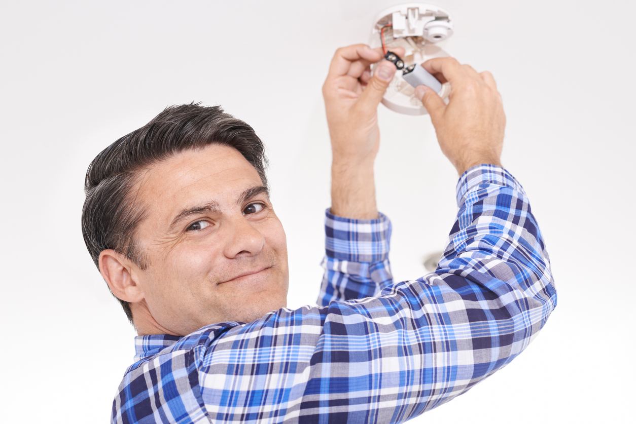 Man Replacing Battery In Home Smoke Alarm