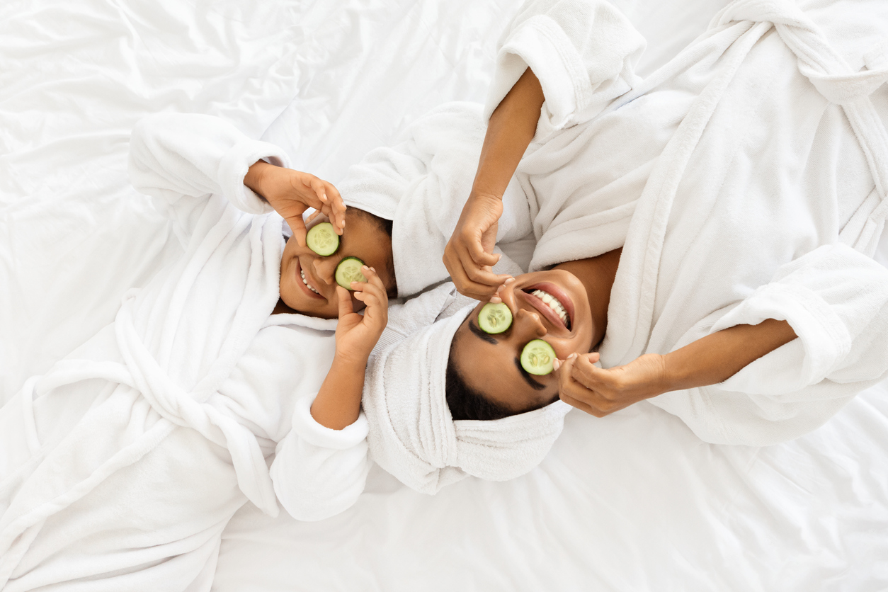 Mom And Daughter In Bathrobes Lying With Cucumber Slices On Eyes, Doing Face Mask Treatment, Wearing Towel On Head, Having Fun Together At Home