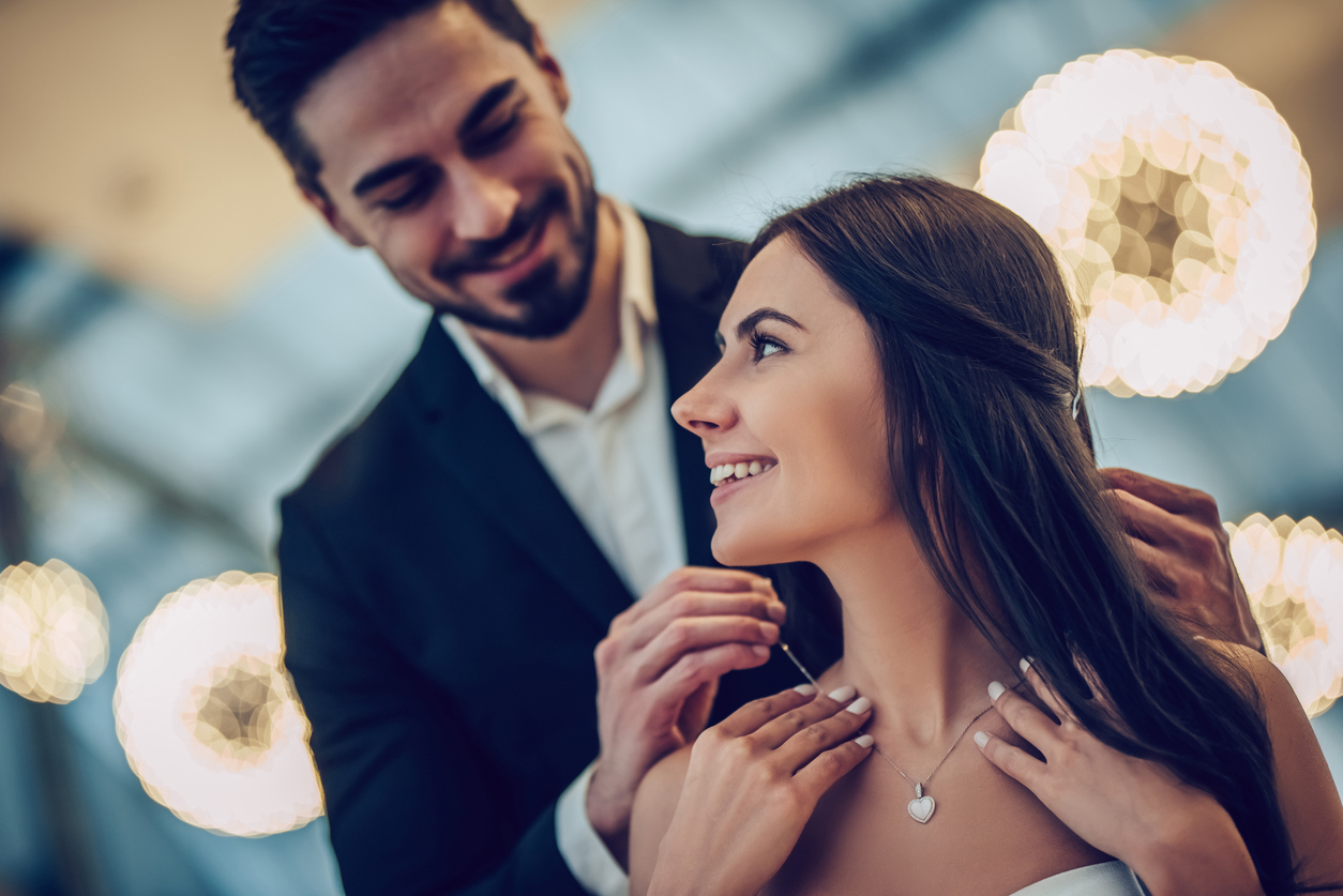 A young couple are having a romantic dinner. Man is giving the woman a beautiful necklace.