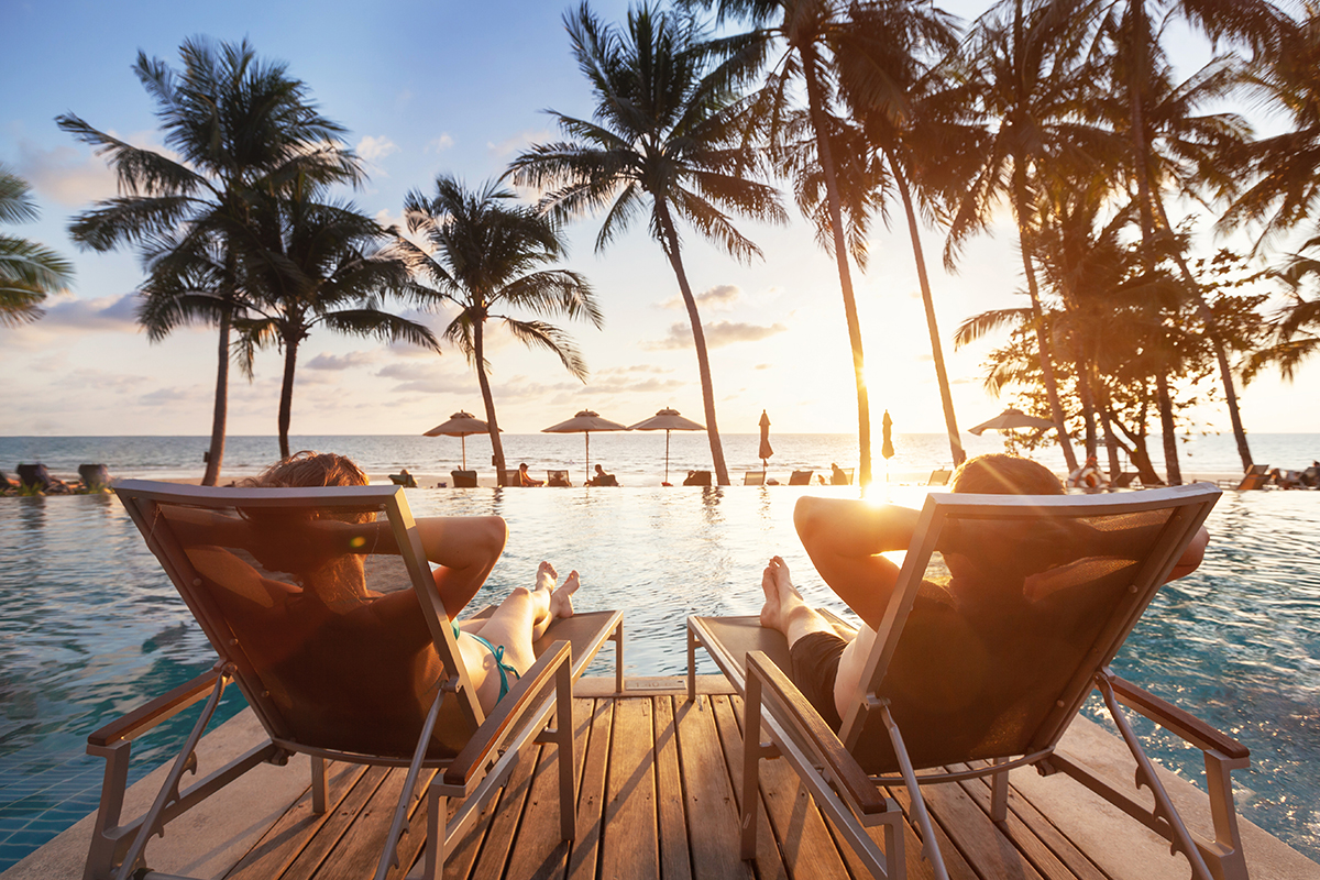 two people sitting in beach chairs at luxury tropical resort in front of sunset