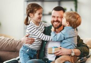 Father hugging two children all smiling and enjoying each other's company