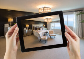 Female Hands Holding Computer Tablet In Room with Photo on Screen.