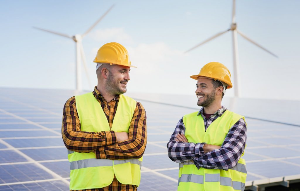 Worker men at solar power station - Solar panels with wind turbines in background