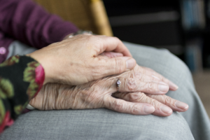 image of senior's hands being comforted by another hand