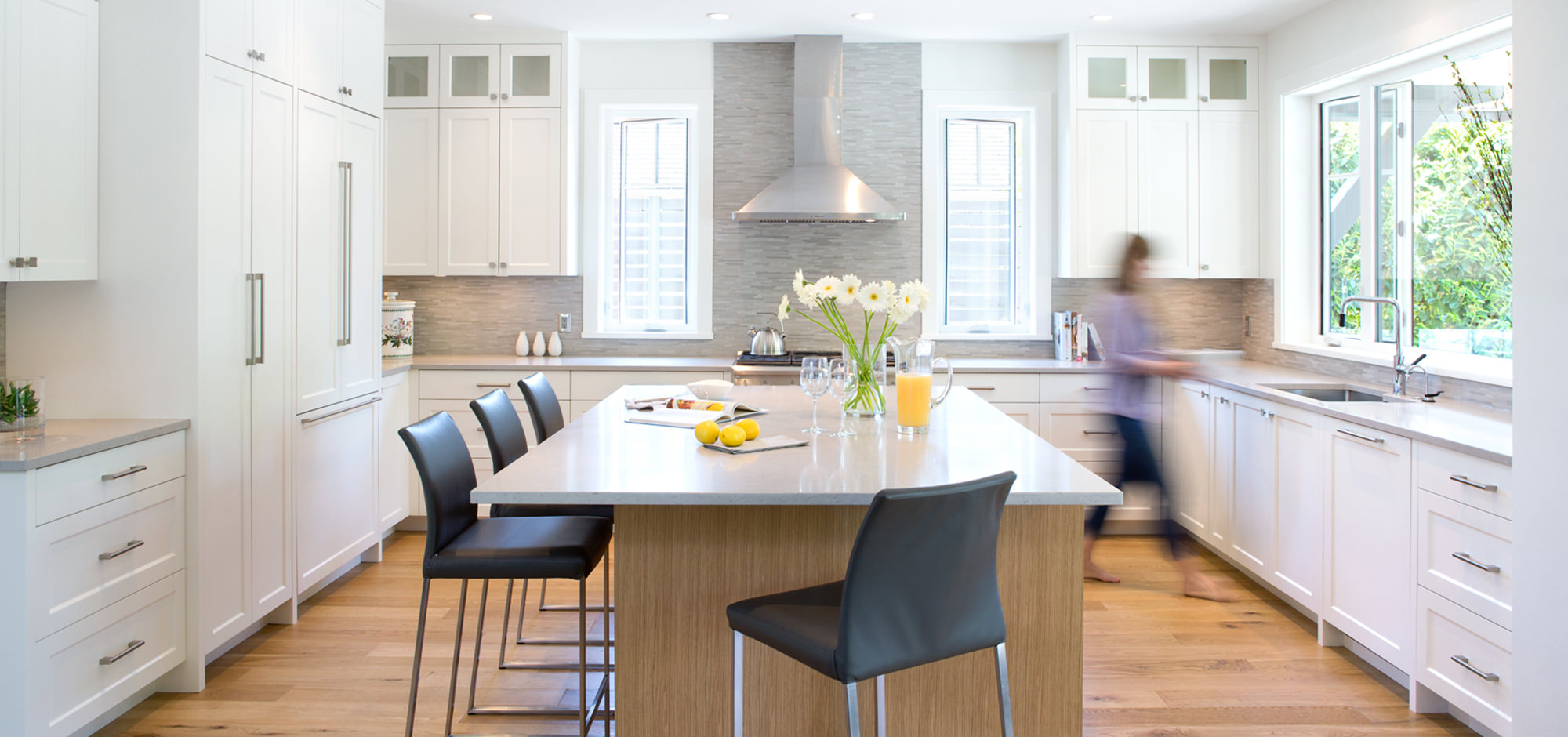 White kitchen with a center aisle countertop and black bar stools