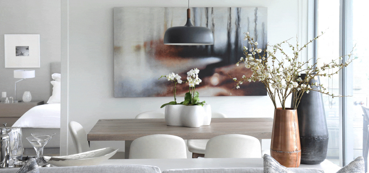 White dinning room with a grey wooden table and decorative flowers in vases