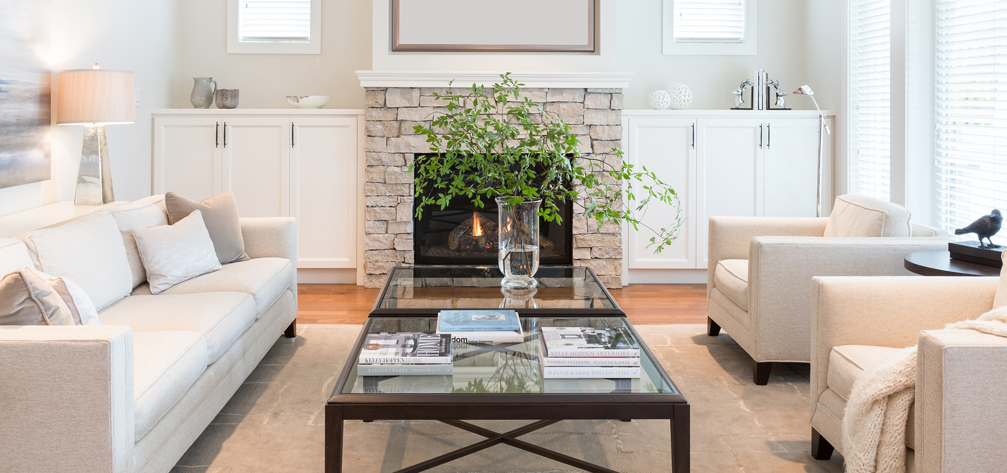 White living room with off-white brick fireplace, white couches, and a glass center table