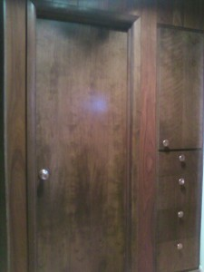 Hall wall paneled with dark wood paneling