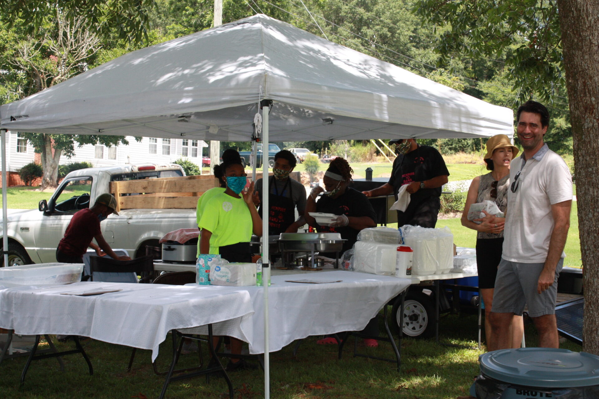 People standing by a table at an event at Pennington Park