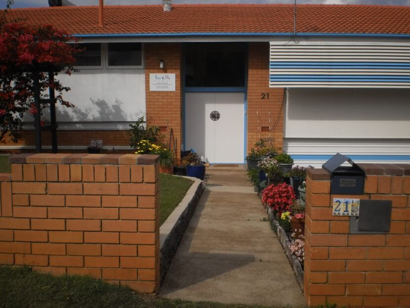 Inviting open gateway and path leading to white double front doors with bright blue trims.