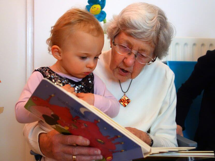 Grandma and very young granddaughter sharing a book.