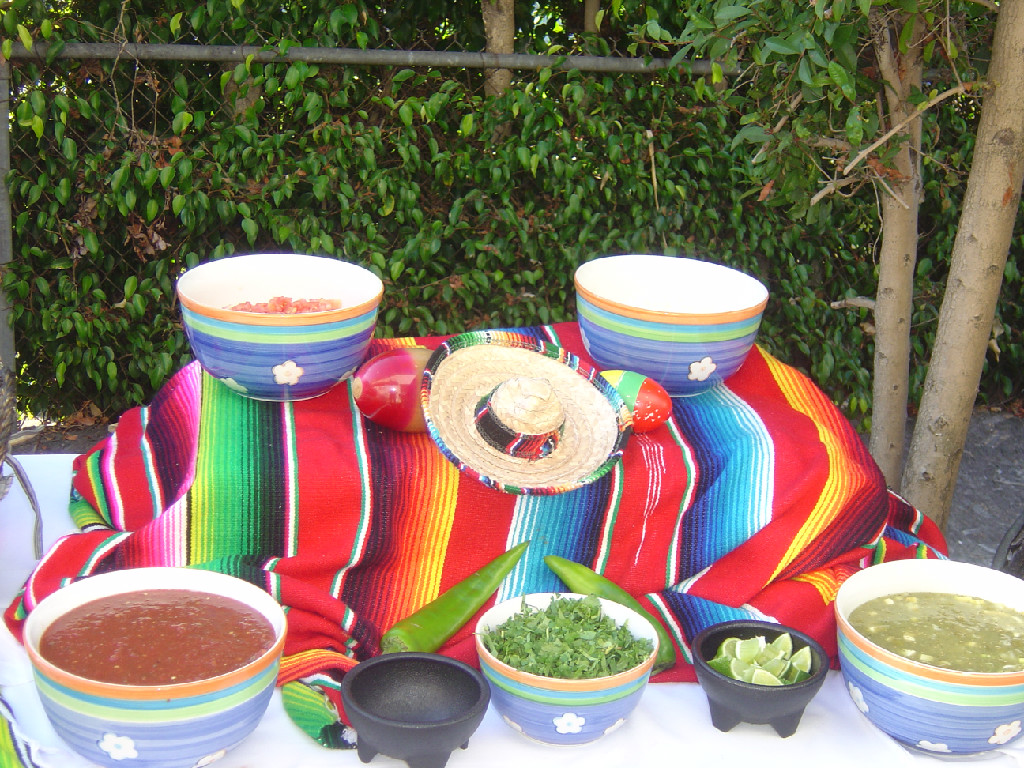 catering table with a multi-colored tableclothe and bowls with assorted salsas and a sombrero