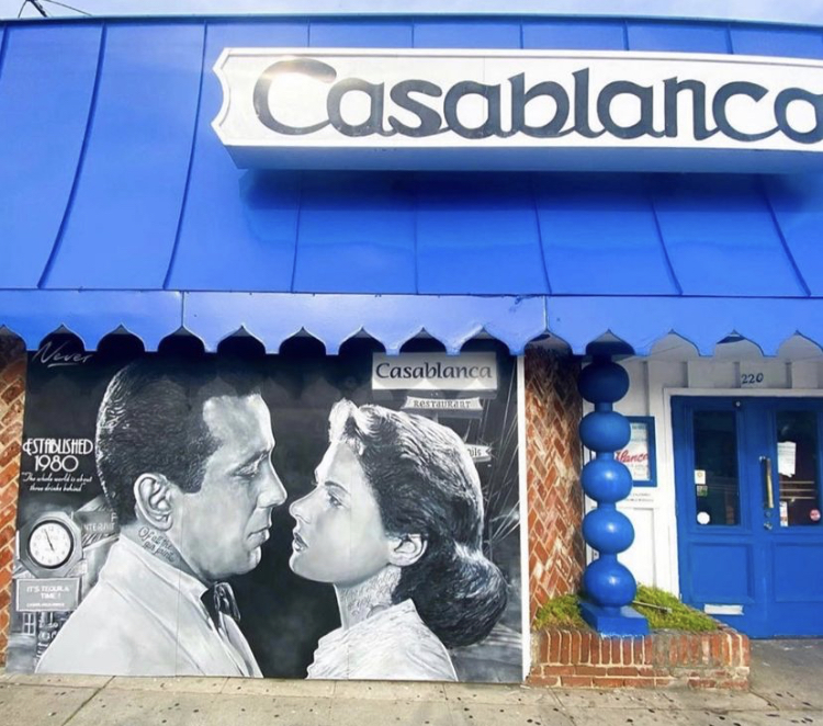 a picture of the front of the restaurant with the name Casablanca at the top and a mural of an scene from the movie Casablanca and a bit of of the front door.