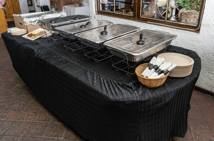 Catering table with wire chafing dishes covered with lids, napkins and plates