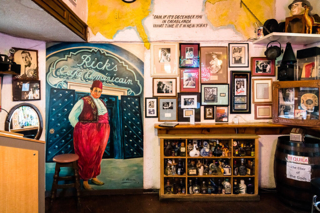 A paining of a scene from the movie Casablanca and a bookshelf with tequila bottles.  The wall above has pictures from the movie Casablanca